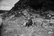 A man taking a break from cutting peat on a stretch of land on the island of Lewis in the Outer Hebrides, Scotland. Peat cutting was a traditional method of gathering fuel for the winter in the sparsely-populated areas on Scotland's west coast and islands. The peat was dried and used in fires and ovens.