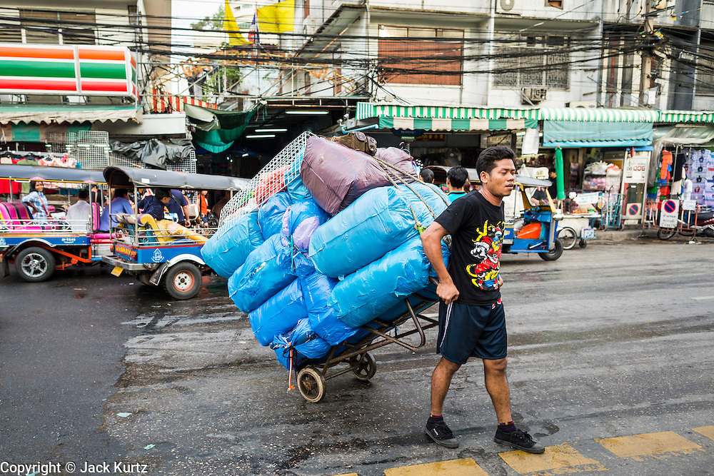 06 JUNE 2013 - BANGKOK, THAILAND:  Porters use handtrucks to haul clothing in wholesale stalls in Bobae Market in Bangkok. Bobae Market is a 30 year old market famous for fashion wholesale and is now very popular with exporters from around the world. Bobae Tower is next to the market and  advertises itself as having 1,300 stalls under one roof and claims to be the largest garment wholesale center in Thailand.       PHOTO BY JACK KURTZ