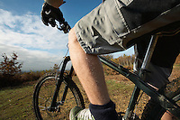 Man riding mountain bike in countryside mid section