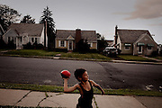 BETHLEHEM, PA &ndash; JUNE 14, 2011: Hector Ortiz, age 9, tosses a football to his uncle John Veanus near their home at 430 Grandview in Bethlehem's Northside. Hector, who is one-half Puerto Rican, is one of many Hispanic children whose families have moved out of the poorer Southside and into the middle class white neighborhoods of the Northside, across the Lehigh River.<br />