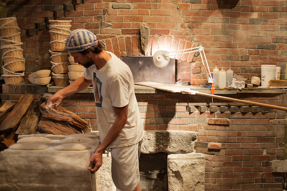 Jamestown, RI - 7 May 2007. Andrea Colognese of The Village Hearth Bakery and Cafe, preparing loaves of bread for the oven.