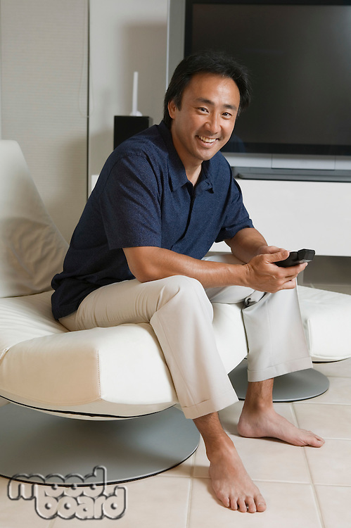 Man Sitting in Modern Living Room Holding Remote portrait