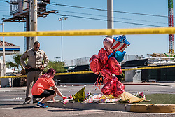 October 3, 2017 - Las Vegas, Nevada, U.S - Unidentified people, accompanied by Las Vegas Sheriff's deputies, place flowers at makeshift memorial on Las Vegas Boulevard near the Mandalay Hotel and the site of Sunday's mass shooting which claimed the lives of 59 people and injured hundreds of others.  The area is still an active crime scene. (Credit Image: © Nick Otto via ZUMA Wire)
