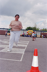 Primary school girl taking part in relay race during P,E, lesson,