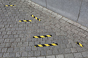 Yellow and black hazard tape on the ground of the pavement in Jubilee Gardens, on 20th July 2017, on the Southbank, London, England.