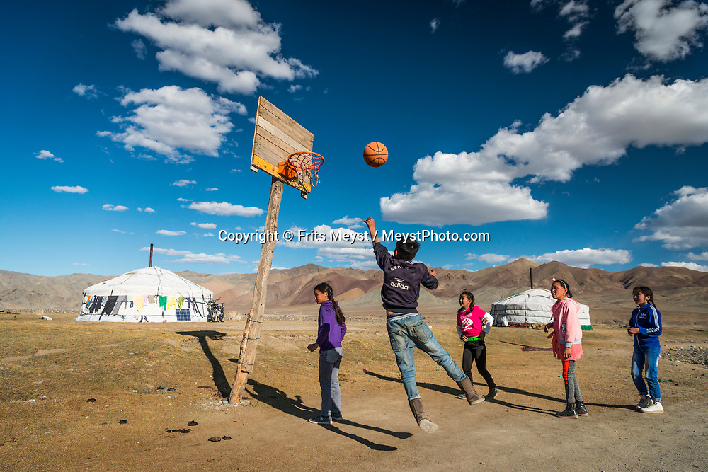 Ulgii, Altai Mountains, Mongolia, September 2017.  Village life on the steppe. Men wrestle while kids play basketball next to the yurt. For centuries, Kazakh men have hunted from horseback with trained golden eagles, the largest and most powerful of raptors. They hunt during winter, when the pelts of the rabbits, red fox and wolf are at their most luxuriant. The hunter is named kusbegi or berkutchi. It takes 5 years to train a golden eagle to hunt, and the skills are transferred from father to son. The Altai Mountains are situated in Western Mongolia on the border with Russia, Kazakhstan and China. Photo by Frits Meyst / MeystPhoto.com