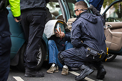 © Licensed to London News Pictures. 07/10/2019. London, UK. Specialist police officers use angle grinders to unlock an Extinction Rebellion protestor from a car blocking the road on Victoria Embankment. Two weeks of action are planned at various locations around Westminster as part of a coordinated protest to call on government to act on climate change. Photo credit: Rob Pinney/LNP
