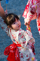 A young girl in traditional kimono looks back at the camera while being held firmly by her mother and grandmother.