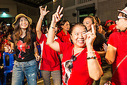 27 JULY 2013 - BANGKOK, THAILAND:  Thai Red Shirts dance during the party for Thaksin Shinawatra. The Red Shirts celebrated former Prime Minister Thaksin Shinawatra's 64th birthday with a party at Phibun Prachasan School in Bangkok. They had a Buddhist Merit Making Ceremony, dinner, cake and entertainment. Most of the Red Shirt political elite traveled to Hong Kong for a party with Thaksin. Thaksin, the former Prime Minister, was deposed by a coup in 2006 and subsequently convicted of corruption related crimes. He went into exile rather than go to jail but remains very popular in rural parts of Thailand. His sister, Yingluck Shinawatra is the current Prime Minister and was elected based on her brother's recommendation.    PHOTO BY JACK KURTZ