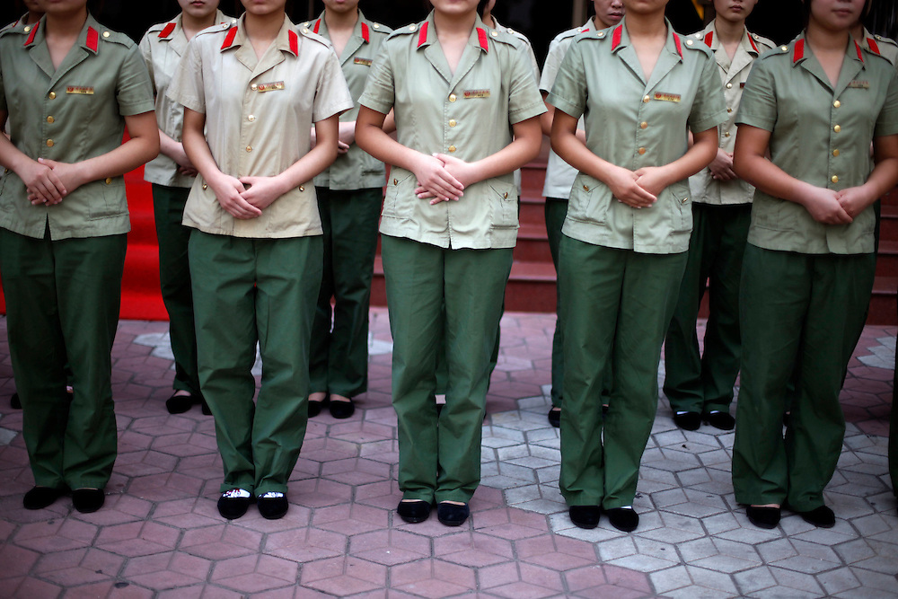 Workers dressed in communist style uniforms sing revolutionary songs ahead of a day's work in the model village of Nan Jie Cun, China, Thursday, Aug. 27, 2009.  Nan Jie Cun village in central China's Henan province advertises itself as a commune which continues to adhere to the communist teachings of Mao Zedong, who founded the People's Republic 60 years ago. The village's industries are collectively owned. Workers receive bonds, instead of currency, and housing and healthcare are free. They sing revolutionary songs and march to work in lines. Despite being out of step with the rest of today's China, the village's industries are a success, and more than 7,000 migrants have requested to work at Nan Jie Cun.