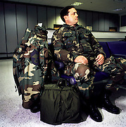 Surrounded by personal effects and baggage, a US airman with the insignia for a Chief Master Sergeant (CMSgt), awaits his flight in the terminal at Mildenhall air force base, Suffolk, England. Leaving England and a posting abroad, the man looks relaxed before a long flight back the USA after duty in Europe.