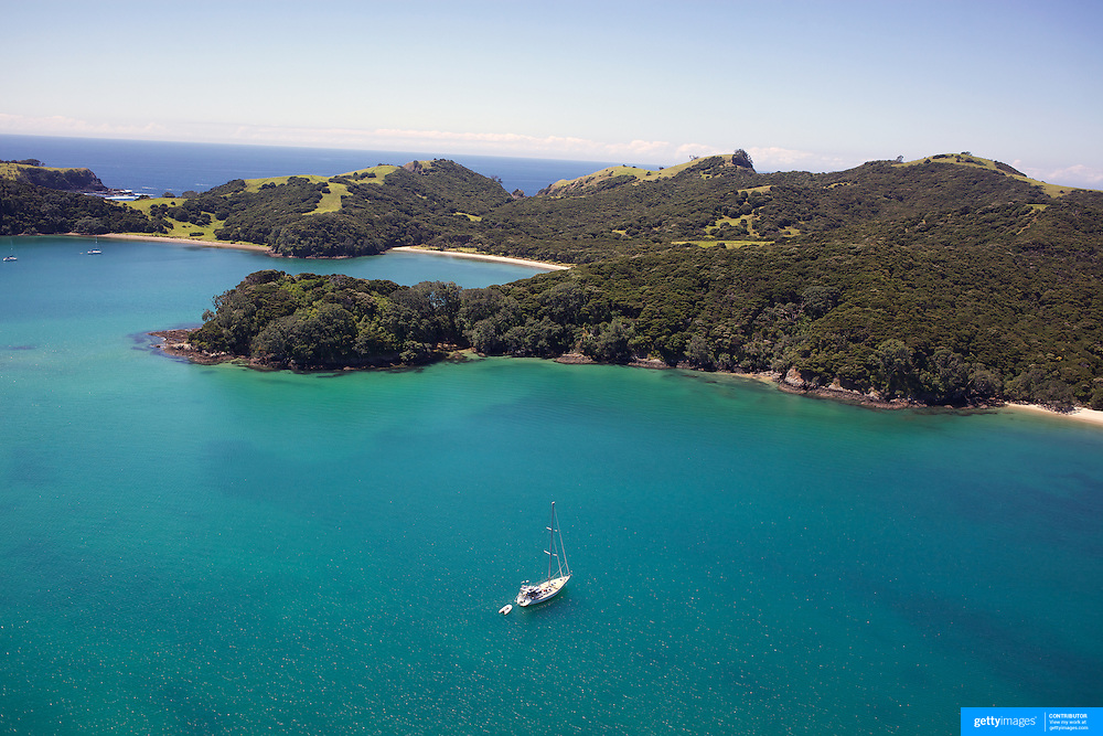 An aerial view of A yacht moored in a secluded bay in the Bay of Islands, North Island, New Zealand. .The Bay of Islands boasts a unique coastline sheltering over 150 small islands in its arms. Once a seafaring and whaling region the Bay of Islands is today a popular tourist destination recognised for it's cultural heritage as well as it's amazing scenery and wildlife. Small towns are scattered along the coastline. There are a lot of water-based activities, including kayaking, swimming with dolphins, game fishing and boating and whales and dolphins can often be seen in the bay. Bay of Islands, New Zealand, 16th November 2010. Photo Tim Clayton.