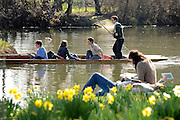 © Licensed to London News Pictures. 11/03/2012. Oxford, UK. A young couple read on the banks of the river as a punt floats past. People enjoy the early morning sunshine on the River Cherwell in Oxford today 11 March 2012. Photo credit : Stephen SImpson/LNP