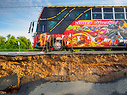 14 JULY 2015 - THAILAND:  A passenger bus drives along a collapsed roadbed in Ayutthaya province. The drought that has crippled agriculture in central Thailand is now impacting residential areas near Bangkok. The Thai government is reporting that more than 250,000 homes in the provinces surrounding Bangkok have had their domestic water cut because the canals that supply water to local treatment plants were too low to feed the plants. Local government agencies and the Thai army are trucking water to impacted communities and homes. Roads in the area have started collapsing because of subsidence caused by the retreating waters. Central Thailand is contending with drought. By one estimate, about 80 percent of Thailand's agricultural land is in drought like conditions and farmers have been told to stop planting new acreage of rice, the area's principal cash crop.      PHOTO BY JACK KURTZ