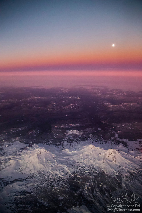 The Three Sisters, a cluster of three volcanic peaks in central Oregon, are bathed in alpenglow as the full moon sets into the Belt of Venus just before sunrise in this aerial view. The three peaks are the third-, fourth- and fifth-highest peaks in Oregon. Of the three, the South Sister, visible on the left, is the tallest with an elevation of 10,385 feet (3,157 meters) and is also known as Charity. The Middle Sister, also known as Hope, is the shortest with an elevation of 10,047 feet (3,062 meters). The North Sister, also known as Faith, is slightly taller at 10,085 feet (3,074 meters). The Three Sisters are unusual in that the volcanic peaks are in a dense cluster; volcanoes in the Cascade Range are typically spaced out with 40 to 60 miles (60 to 100 kilometers) of distance between them. Of the three peaks, only the South Sister is likely to become active again. The last eruption was 50 B.C. The Three Sisters are part of the Three Sisters Wilderness, Oregon's second-largest wilderness area.