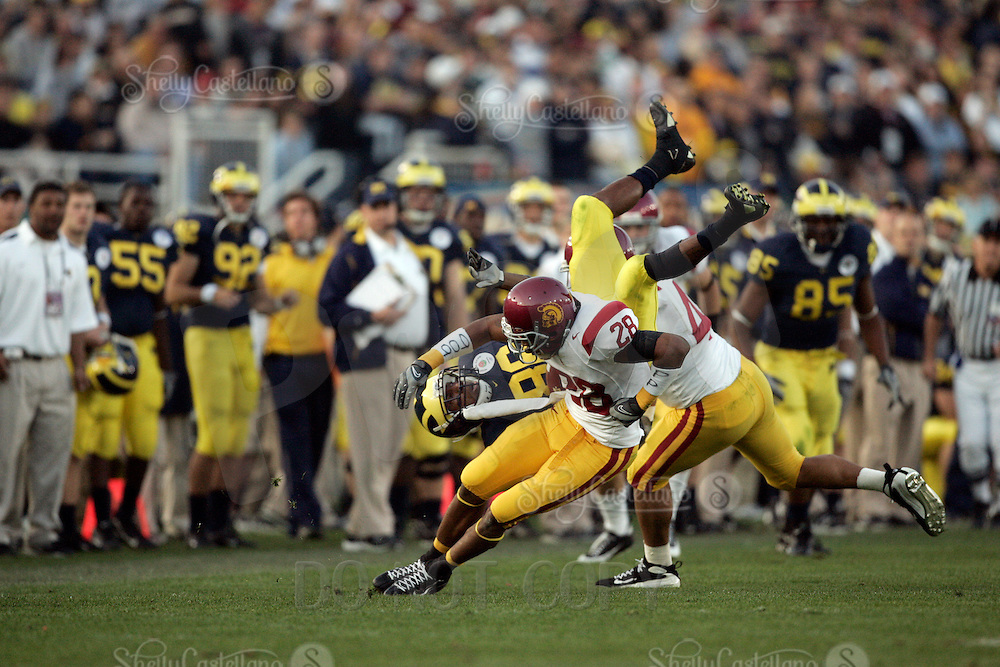 1 January 2007:  Mario Manningham is tackled down by Terrell Thomas at the 93rd Rose Bowl Game at the Rose Bowl Stadium for the Pac-10 USC Trojans vs the Big-10 Michigan Wolverines NCAA college football game in Southern California.  Trojans defeated the Wolverines 32-18 in regulation.<br />
