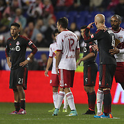 Thierry Henry, New York Red Bulls, holds back Michael Bradley, Toronto FC, as he argues with the referee Hilario Grajeda, (left), during the New York Red Bulls Vs Toronto FC, Major League Soccer regular season match at Red Bull Arena, Harrison, New Jersey. USA. 11th October 2014. Photo Tim Clayton