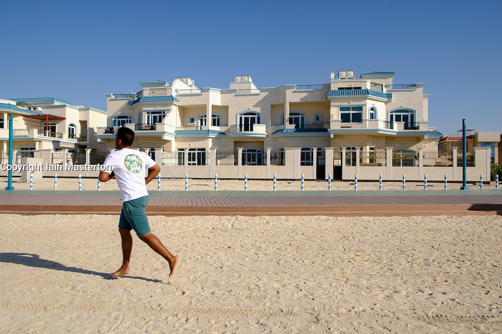 Man jogging past luxury villas facing onto beach in Dubai United Arab Emirates