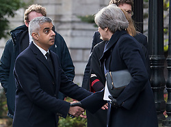 © Licensed to London News Pictures. 14/12/2017. London, UK. Mayor of London SADIQ KHAN shakes the hand of British prime minister THERESA MAY as they leave St Paul's Cathedral in London following the Grenfell Tower National Memorial Service mark the six month anniversary of the Grenfell Tower fire. The service is attended by survivors of the fire and relatives of those who lost their lives in the fire, as well as members of the emergency services and members of the Royal family.  Over 70 people were killed when a huge fire ripped though 24-storey Grenfell Tower block in west London in June 2017.   Photo credit: Ben Cawthra/LNP