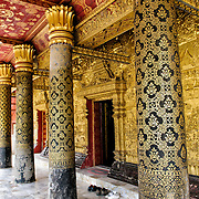 Columns outside Wat Mai Suwannaphumaham.  Wat Mai (or Wat May), as it is often known, is a Buddhist temple in Luang Prabang, Laos, located near the Royal Palace Museum. It was built in the 18th century and is one of the most richly decorated Wats in Luang Prabang.