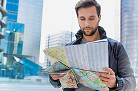 Portrait of young attractive man looking on the map in the city