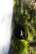 A young woman, holds a safety cable and leans over a cliff to get a better view of Tunnel Falls on the Eagle Creek trail in the Columbia River Gorge, Oregon, USA.  Tunnel Falls received its name due to a tunnel being cut from the bedrock behind the falls so that hikers and trail runners can pass further up the gorge.  The trail becomes very narrow during this section and it is necessary to hold onto a safety cable. (Model Released)