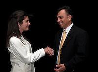 Hispanic boss congratulates his secretary with a handshake.