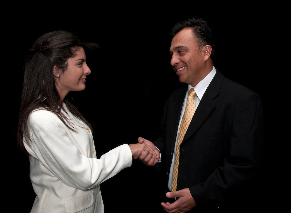 Hispanic boss congratulates his secretary with a handshake.