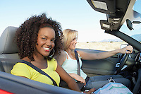 Two women sitting in convertible car on desert road