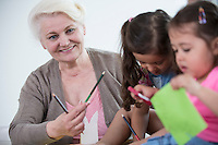 Portrait of senior woman helping granddaughters in making handicrafts at home