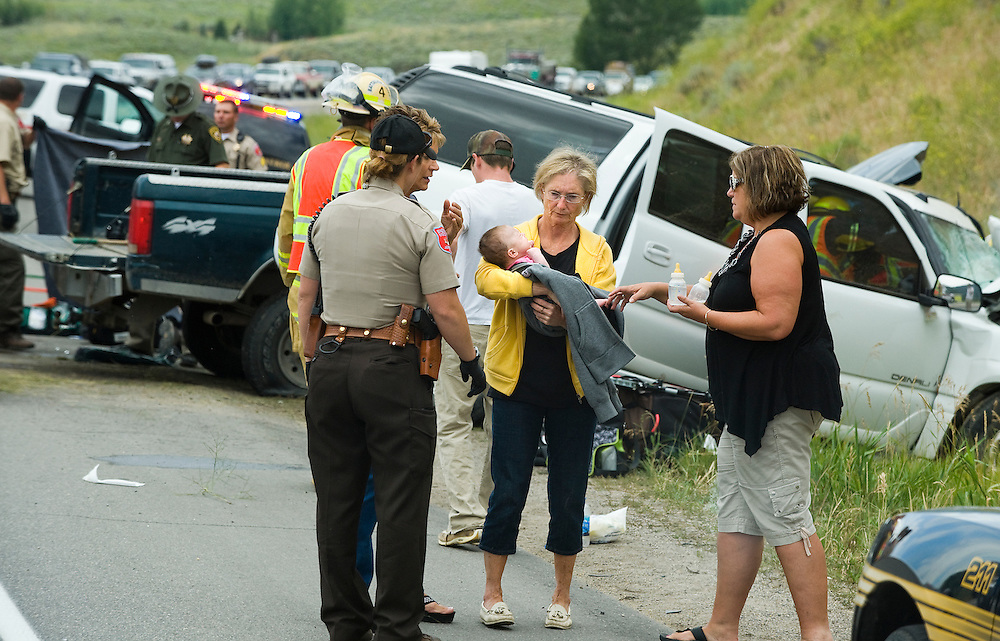 PRICE CHAMBERS / NEWS&GUIDE.First responders tend to victims of two locals' vehicles involved in a fatal collision Monday on Hwy. 22 as a woman holds a crying baby that survived the crash.