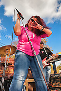 "Making ""Rock on"" ""horns"" (corna) hand gesture is Blues singer Sweet Suzi Smith, performing with guitarist John Puglisi of ""Sweet Suzi and Sugafixx"" n outdoor stage at Merrick Street Fair in Merrick, New York, USA, on October 22, 2011"