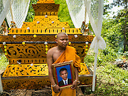 20 JUNE 2016 - DON KHONE, CHAMPASAK, LAOS: A Buddhist monk holds a picture of his father before the man's cremation in the jungle near Don Khone village on Don Khone Island. Don Khone Island, one of the larger islands in the 4,000 Islands chain on the Mekong River in southern Laos. The island has become a backpacker hot spot, there are lots of guest houses and small restaurants on the north end of the island. In the southern Lao funeral tradition, the deceased is cremated at the place of his choosing, usually a place he (or she) was especially fond of. In this case, the man chose to be cremated in a small clearing in the jungle a few kilometers from his home.     PHOTO BY JACK KURTZ