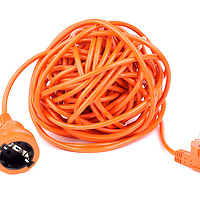 An orange electrical cable wound up into a ball