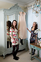 Sisters holding dress hanged on hanger