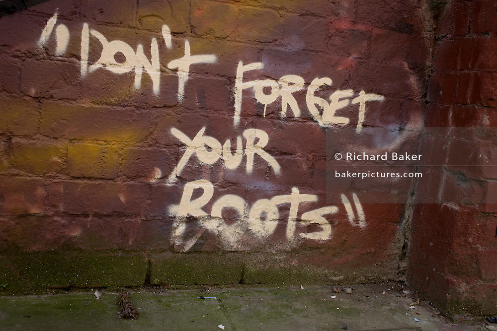 The words 'Don't Forget Your Roots' written in graffiti near Brick Lane, east London.