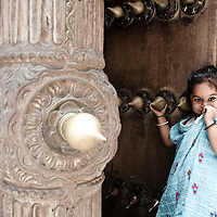 A young girl looks out of a doorway in Stonetown, Zanzibar