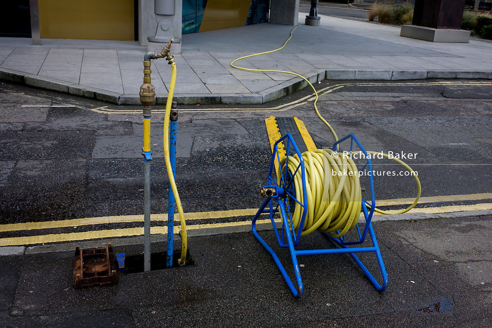 Yellow hosepipe stretched across road with coincidental double-yellow lines.