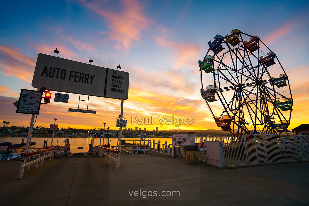 Newport Beach California Balboa Fun Zone high resolution sunrise photo. Includes the Balboa Island Auto Ferry sign, Ferris Wheel, Newport Harbor, and Balboa Island. Newport Beach is a popular coastal city along the Pacific Ocean in Orange County Southern California. Copyright ⓒ 2017 Paul Velgos with All Rights Reserved.