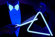 A man in formal attire strikes a glowing triangle.Black light