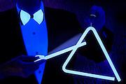 A man in formal attire strikes a glowing triangle.Black light
