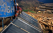 Near piles of wood, a local hotel owner makes adjustments to solar panels in the remote Himalayan village of Ghorepani.
