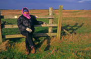 A08AJC Woman wrapped up in winter clothes sits stile