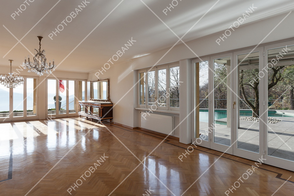 interior of an house, empty room with many windows, parquet floor and white walls