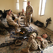 29 April 2004....Baghdad, Iraq.....US troops in Sadr city.....Troops from 2 Cav have the responsibility for patroling the streets of Baghdads most violent nieghbourhood, Sadr city...The residents are amoung Baghdads poorest with a high level of unemployment, the firebrand cleric Moqtada al Sadr has great support in this area and it has recently been the scene of violent clashes. His followers took over several buildings and the US forces have fought to regain control...The soldiers report that they are attacked nightly with riflefire, rocket propelled grenades and mortars.....Specialist Bobby Lisek (standing) tells of a lucky escape during a recent rooftop raid. He became entangled in a washing line that pulled him backwards, as it did so two bullets ripped through his webbing and uniform. One round smashed his radio and another scorched his arm.