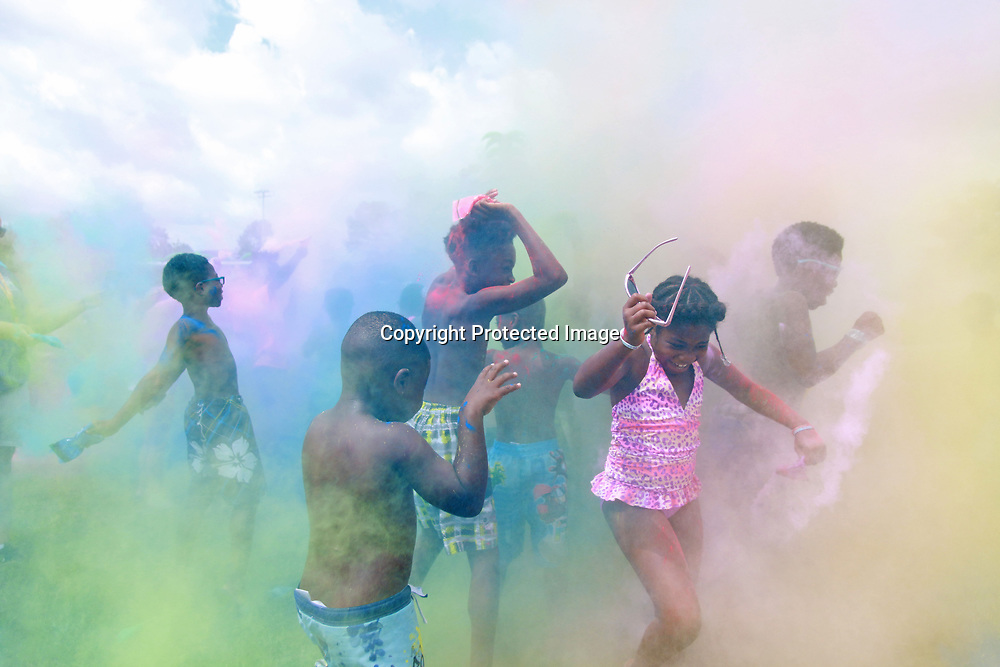 "6-year-old Jaiden Ware, 10-year-old Kameron coguins, and 9-year-old Kamaria Guyton jump arount in a brilliant haze of color during the color run portion of Tupelo Park and Rec's ""Super Fun Day"" Friday morning."