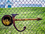 21 APRIL 2017 - CHANHASSEN, MN: A piece of wood carved in the shape of Prince's famous guitar hanging on the fence in front of Paisley Park, the former home and recording studio of Prince. The superstar died from an accidental overdose of the opioid fentanyl on April 21, 2016. Friday was the first anniversary of his death. Crowds of people gathered at Paisley Park, which is now a museum, to honor the Minnesota born musician.     PHOTO BY JACK KURTZ