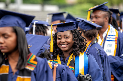 A smiling Howard student in regalia among her peers.