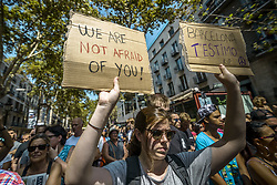 August 18, 2017 - Barcelona, Catalonia, Spain - A mourner with her placards pass through Las Ramblas after a minute's silence for Barcelona's attacks victims after a van ploughed into crowds in Las Ramblas, killing at least 13 people and injuring more than 100 (Credit Image: © Matthias Oesterle via ZUMA Wire)