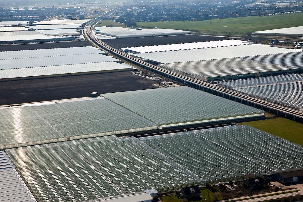 Nederland, Zuid-Holland, Bleiswijk, 20-03-2009; spoorbaan van de HSL doorsnijdt het kassengebied Hoefweg-Zuid in de Overbuurtsche Polder. De rails buigen af richting Rotterdam, aan de horizon links Bergschenhoek, rechts Berkel en Rodenrijs. The railway of the HST crosses the greenhouses area. Swart collectie, luchtfoto (toeslag); Swart Collection, aerial photo (additional fee required); .foto Siebe Swart / photo Siebe Swart